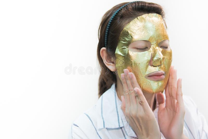 Junges schönes asiatisches weibliches Händchenhalten nahe Haupt- und goldener Maske auf Gesichtshaut stockbilder