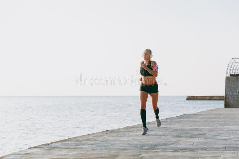 Junges schönes athletisches Mädchen mit dem langen blonden Haar in den Kopfhörern hörend auf Musik und Betrieb bei Sonnenaufgang  lizenzfreie stockfotos
