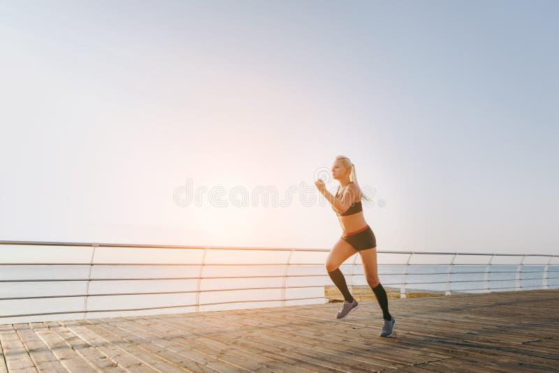 Junges schönes athletisches Mädchen mit dem langen blonden Haar in der schwarzen Kleidung, die bei Sonnenaufgang über dem Meer lä stockfotos