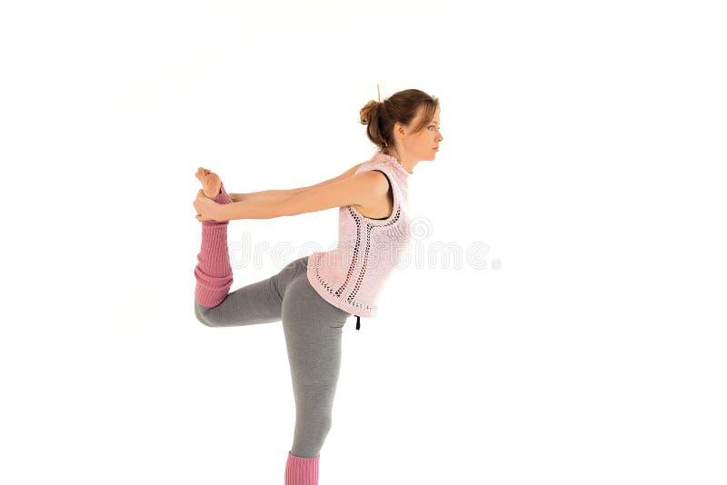 Junges schönes blondes Mädchen, das ihren Fuß, übende Eignung pilates wellenartig bewegt stockfoto