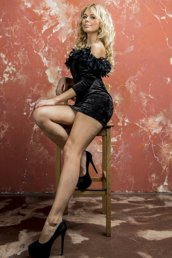 Junges schönes blondes Mädchen in einem schwarzen Cocktailkleid stockfoto
