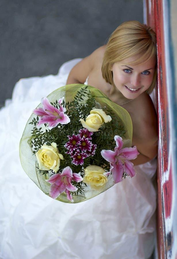 Junges schönes blondes Mädchen mit einem Blumenstrauß von Blumen stockfotos