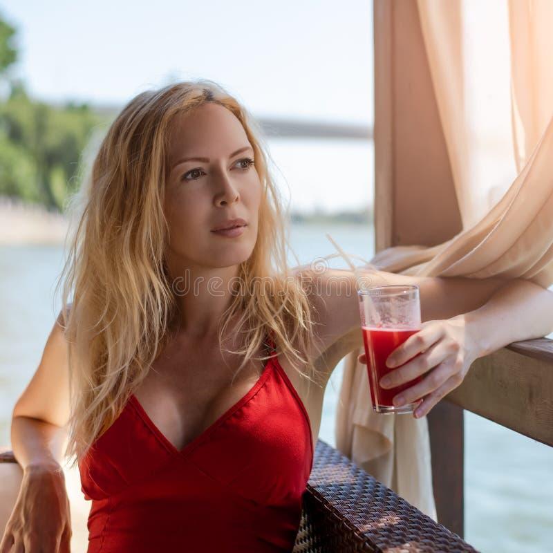 Junges schönes blondes Mädchen sitzt im Sommercafépavillon draußen und hält ein Glas von stockfotografie