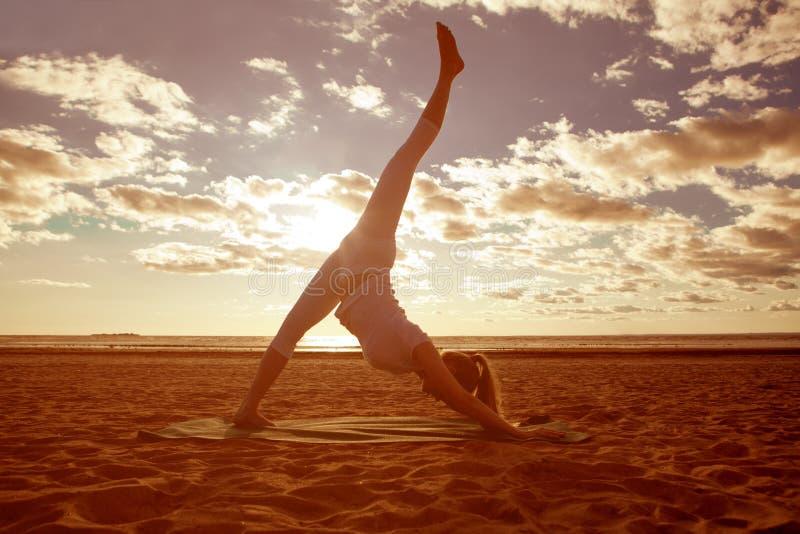 Junges schönes dünnes Frauenschattenbild übt Yoga auf dem beac lizenzfreies stockbild