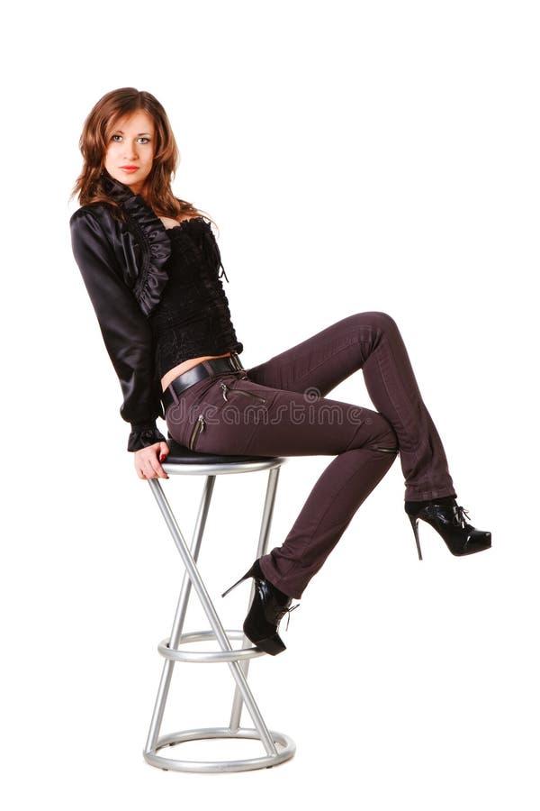 Junges schönes elegantes Mädchen im Schwarzen auf Stuhl lizenzfreie stockfotos