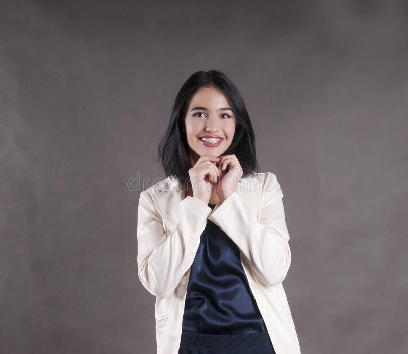 Junges schönes glückliches Geschäftsfrau joyfulexpression stützt Brunettestudio ab lizenzfreie stockfotografie