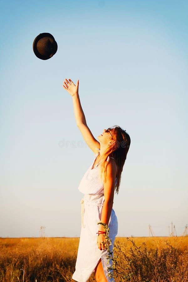 Junges schönes glückliches Mädchen, das ihren Hut in der Luft wirft stockbild