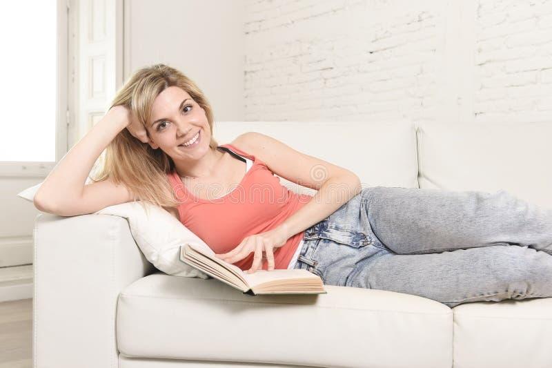 Junges schönes kaukasisches Frauenlesebuch, welches das Lügen bequem auf dem Hauptsofa schaut glücklich studiert stockfoto