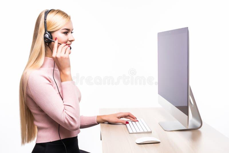 Junges schönes Kundendienst-Betreibermädchen im Kopfhörer, sitzend am Schreibtisch lokalisiert auf weißem Hintergrund lizenzfreie stockfotografie