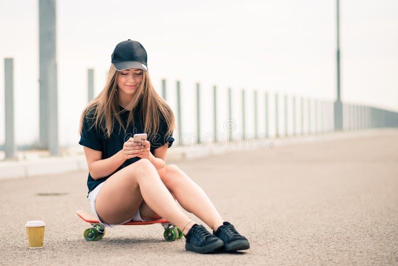 Junges schönes lächelndes blondes Mädchen, das Smartphone beim Sitzen auf dem Skateboard verwendet stockfotos