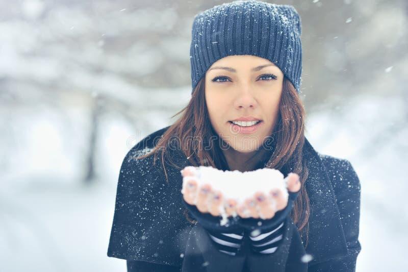 Junges schönes lächelndes Mädchen, das Schnee in den Händen hält stockfotografie