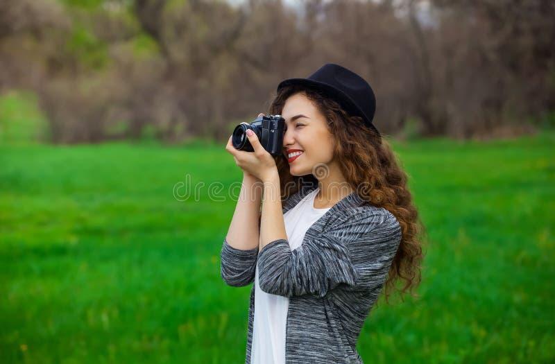 Junges, schönes, lächelndes Mädchen in einem Hut und mit Bildern des langen, gelockten Haares der Natur im Parkfilm lizenzfreies stockbild