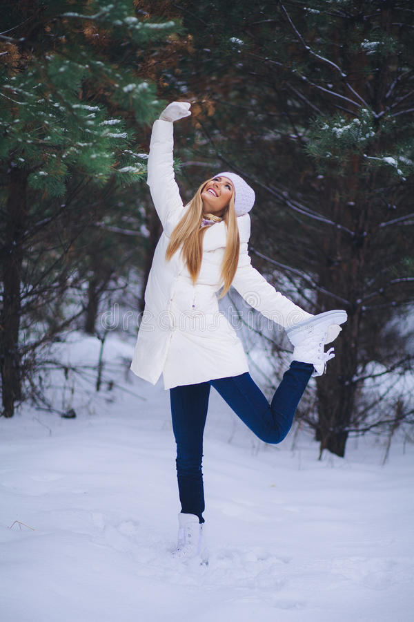 Junges schönes lächelndes Mädchenporträt im Winterwald lizenzfreies stockfoto