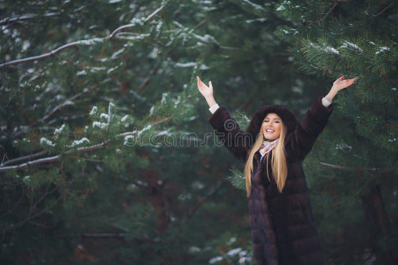 Junges schönes lächelndes Mädchenporträt im Winterwald stockfoto
