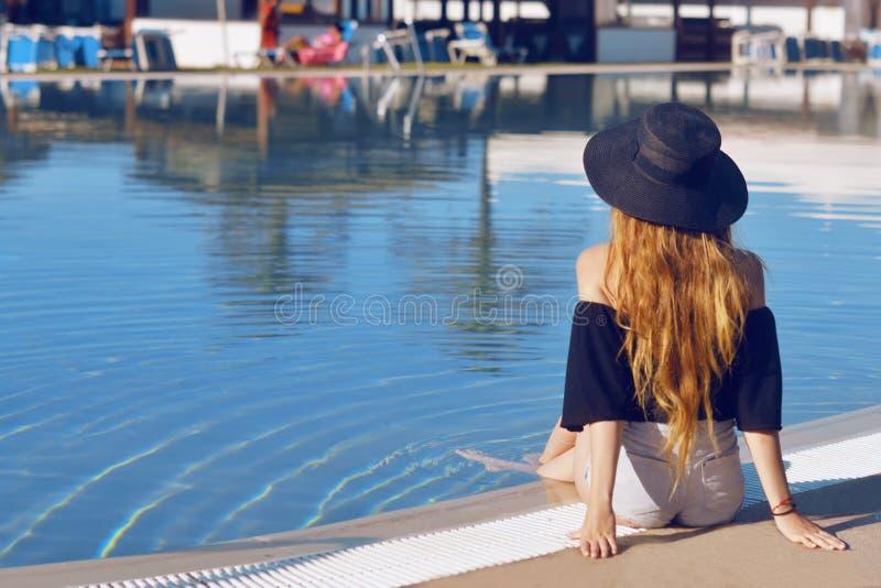 Junges schönes Lächelnmädchen im schwarzen Modehut, in den roten Lippen und langen im Haar, werfend nahe Pool beackground von Pal stockfotografie