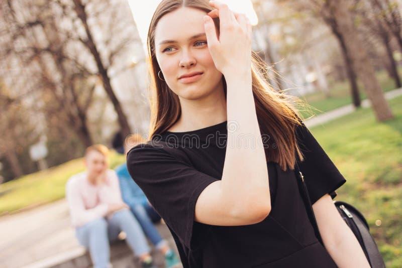 Junges schönes langes Haarmädchen auf dem Hintergrund mit zwei Freunden in der Stadtstraße lizenzfreie stockfotografie