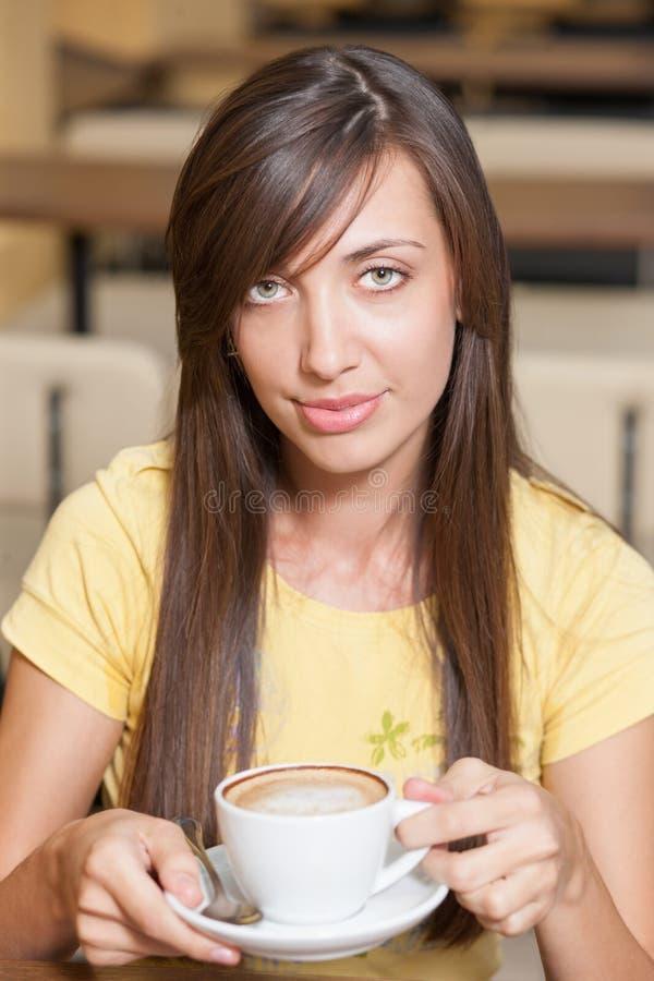 Junges schönes Mädchen über Tabelle mit Cup lizenzfreies stockbild