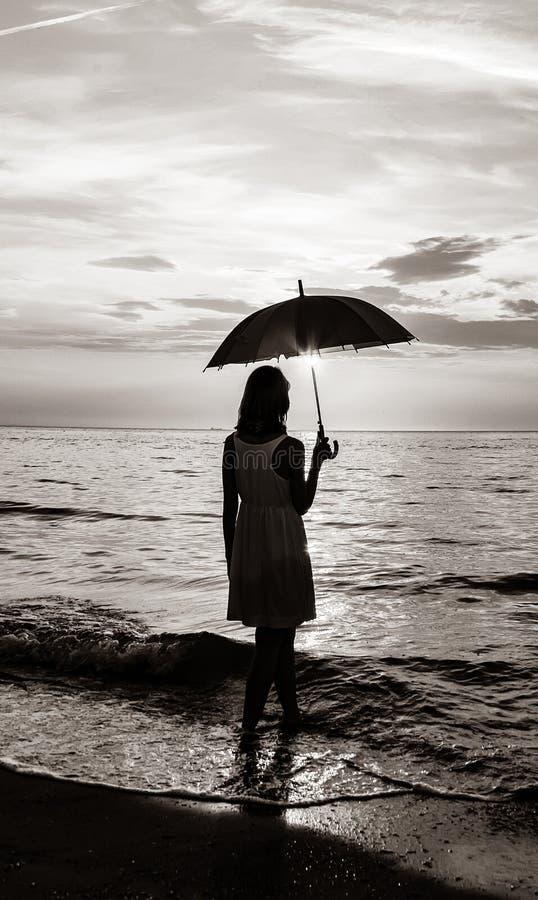 Junges schönes Mädchen auf dem Strand bei Sonnenaufgang mit Regenschirm lizenzfreies stockfoto