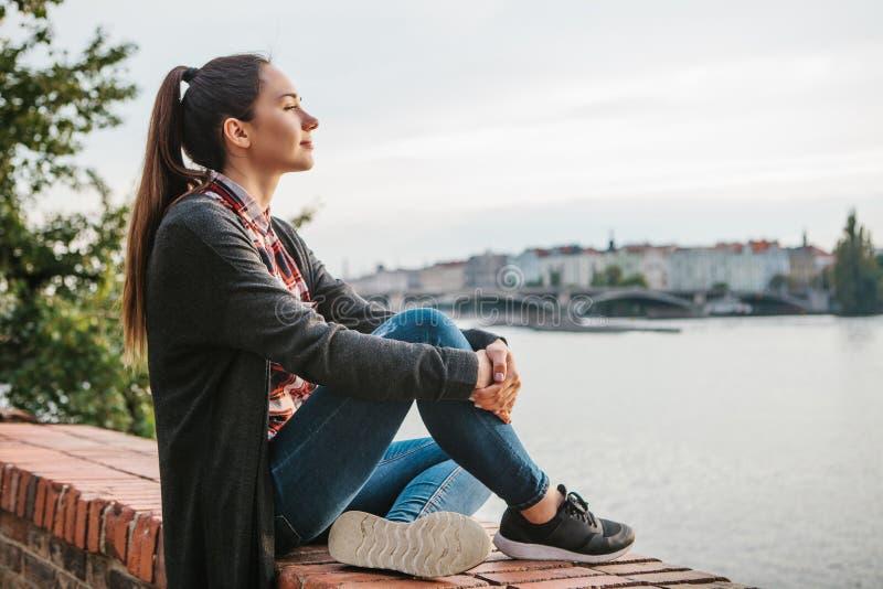 Junges schönes Mädchen auf der Bank des die Moldau-Flusses in Prag in der Tschechischen Republik, die schöne Ansicht bewundernd u stockfotografie