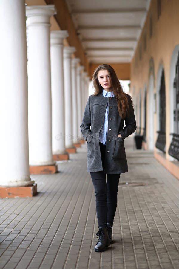 Junges schönes Mädchen auf einem Weg nahe Gebäude mit einer Spalte lizenzfreies stockfoto