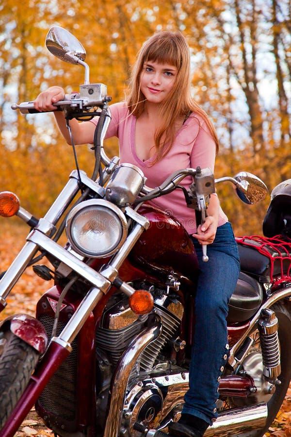 Junges schönes Mädchen auf Motorrad stockbilder