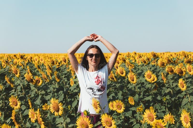 Junges schönes Mädchen, das in den Sonnenblumen steht und oben Hände anhebt Freiheits-Lebensstil-Reise-Konzept lizenzfreie stockfotos