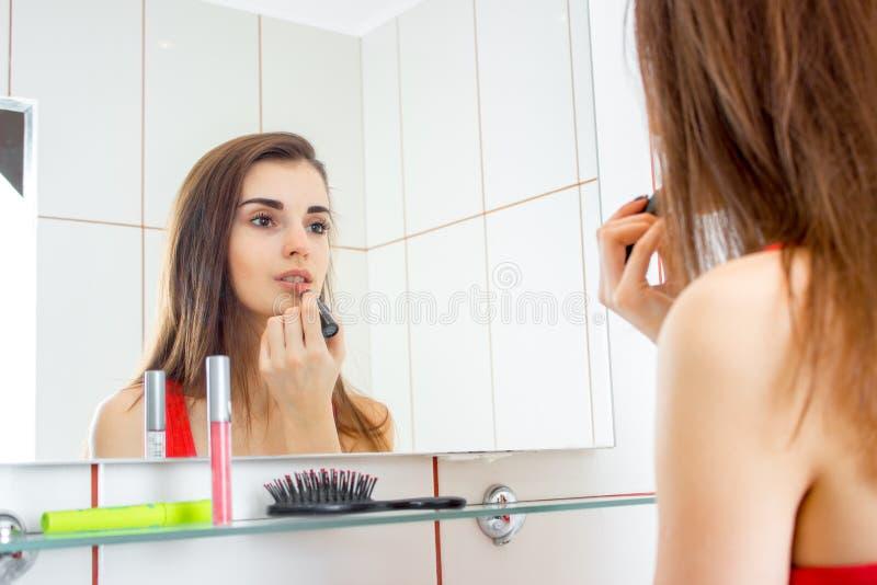 Junges schönes Mädchen, das in der Badezimmerfront des Spiegel- und Farbenlippenlippenstifts steht lizenzfreie stockfotos