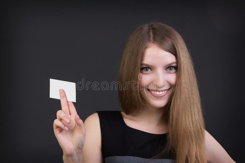 Junges schönes Mädchen, das in der Hand eine Visitenkarte hält stockfotos