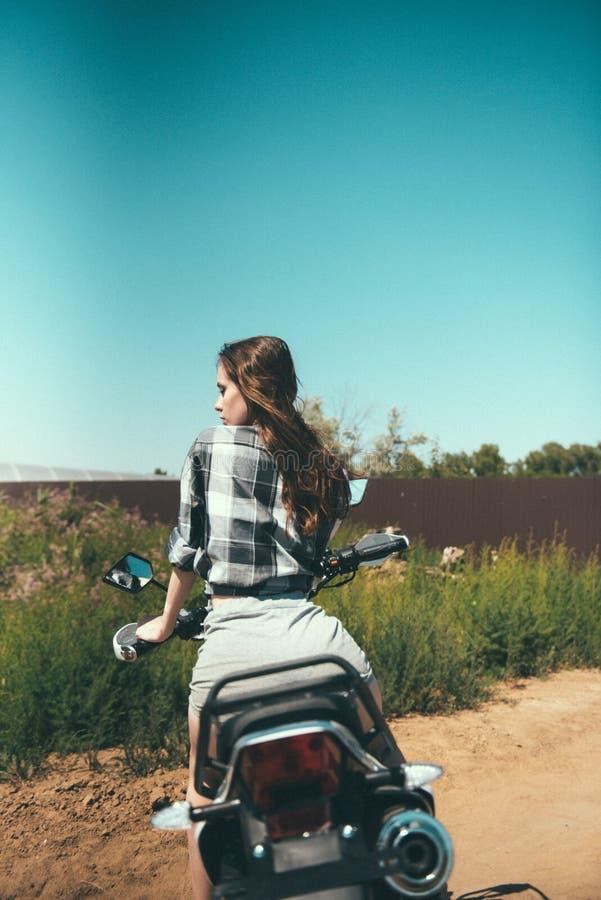 Junges schönes Mädchen, das draußen Sitzen auf einem Motorrad aufwirft lizenzfreie stockfotografie