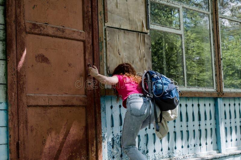 Junges schönes Mädchen, das durch blockiertes Fenster schaut stockbilder