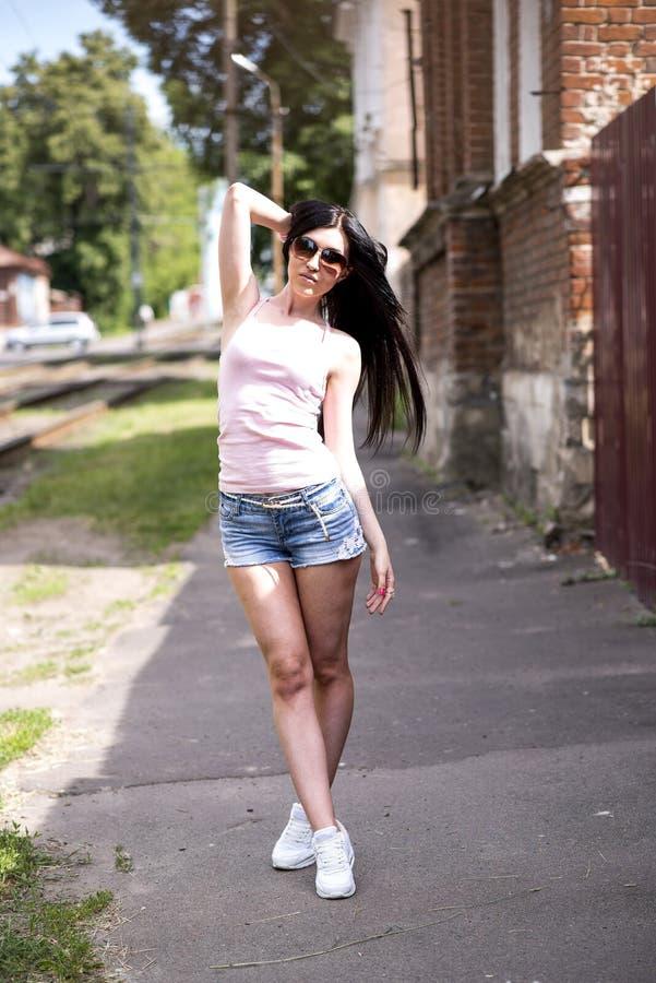 Junges schönes Mädchen, das eine Modestadt in den kurzen Denimkurzen hosen, in der Bluse und in der sexy Frau der Sonnenbrille au lizenzfreie stockbilder
