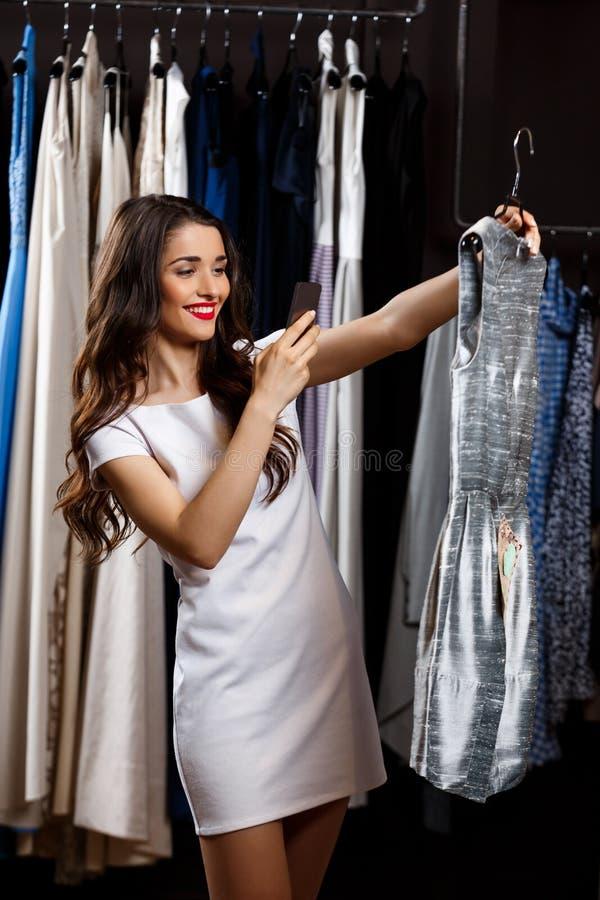 Junges schönes Mädchen, das Foto des Kleides im Einkaufszentrum macht stockbild