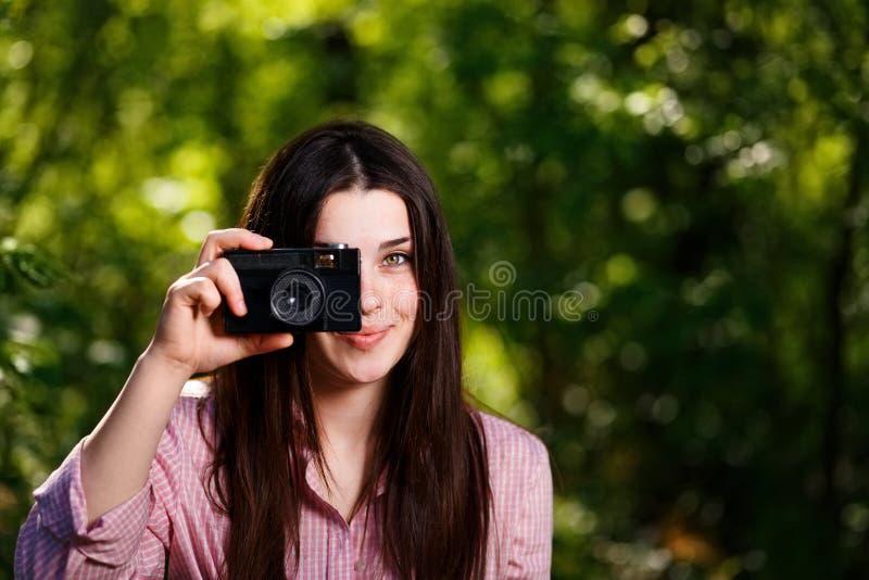 Junges schönes Mädchen, das Fotos mit Retro- Filmkamera in macht stockfoto