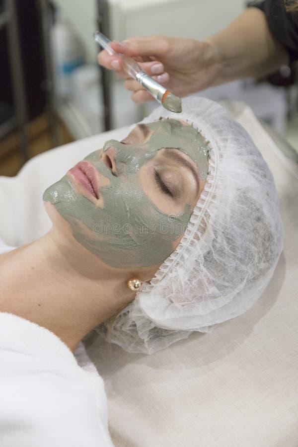 Junges schönes Mädchen, das Gesichtsmaske im Badekurortschönheitssalon - zuhause empfängt lizenzfreie stockfotos