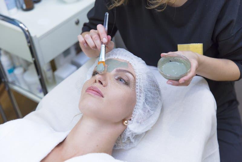 Junges schönes Mädchen, das Gesichtsmaske mit Bürste im Badekurortschönheitssalon - zuhause empfängt stockbild