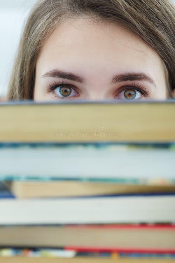 Junges schönes Mädchen, das hinter einem Stapel Büchern in der Bibliothek sich versteckt lizenzfreie stockfotografie