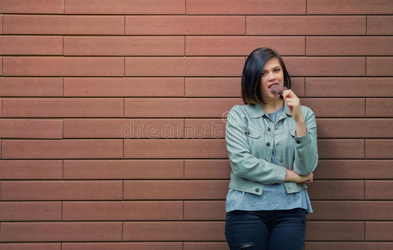 Junges schönes Mädchen, das SchokoladenEiscreme auf einem Stock isst stockfoto