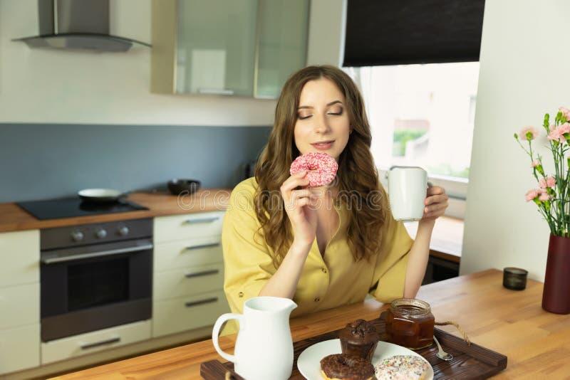 Junges schönes Mädchen, das zu Hause in der Küche frühstückt lizenzfreies stockbild