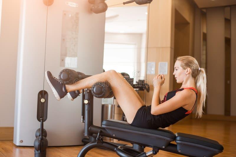 Junges schönes Mädchen in den kurzen Sportkurzen hosen in der Eignung in der Turnhalle rüttelt Bauchmuskeln auf Sporttrainer stockfotografie