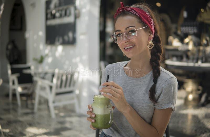 Junges schönes Mädchen in den stilvollen Gläsern und in einem grauen T-Shirt, trinkt exotisches grünes Cocktail im Café im Freien stockfoto