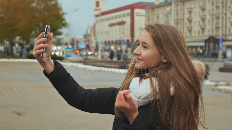 Junges schönes Mädchen in der Jacke tut selfi Herbst in einer der Stadtstraßen lizenzfreies stockbild