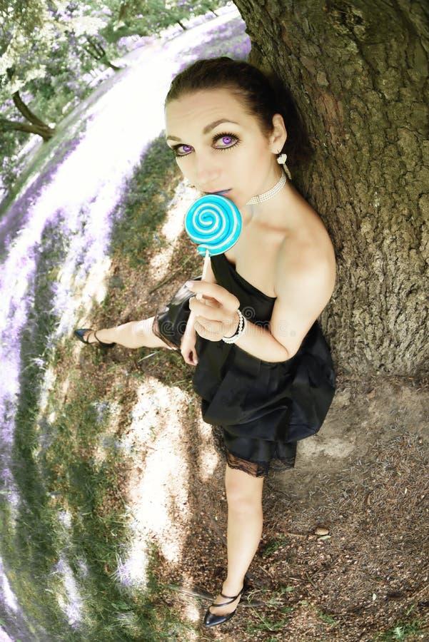 Junges schönes Mädchen des Porträts, das über Baum mit Lutschersüßigkeit sitzt stockbild
