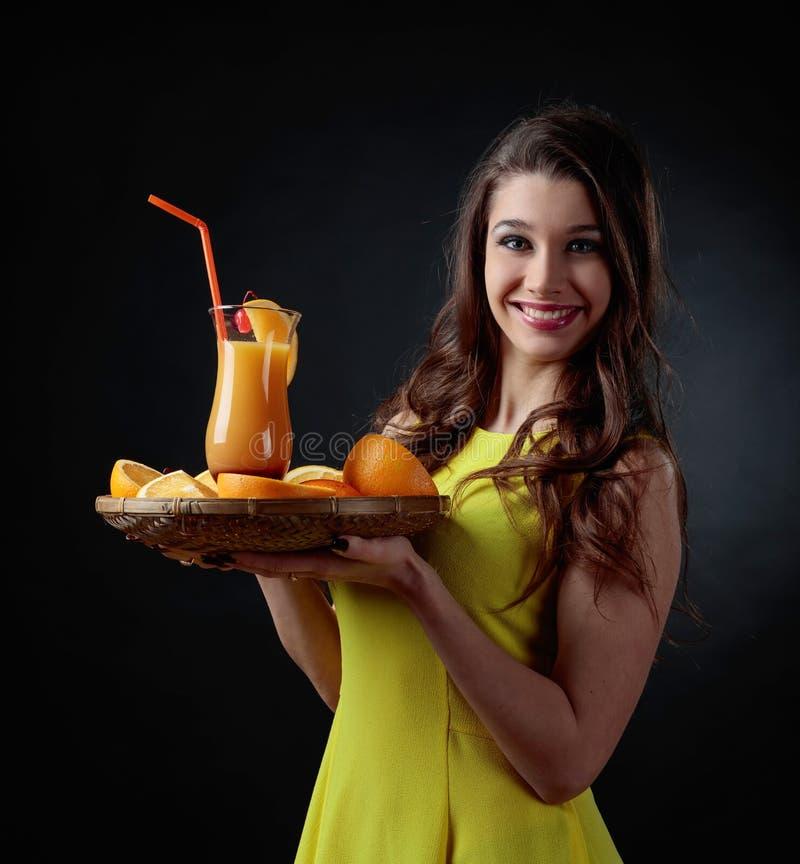 Junges schönes Mädchen in einem gelben Kleid mit Cocktail Tequila Sun stockfoto
