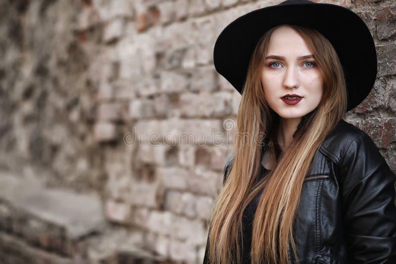 Junges schönes Mädchen in einem Hut und mit einem dunklen Make-up draußen g stockbild