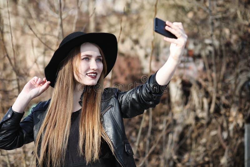 Junges schönes Mädchen in einem Hut und mit einem dunklen Make-up draußen g lizenzfreie stockfotos