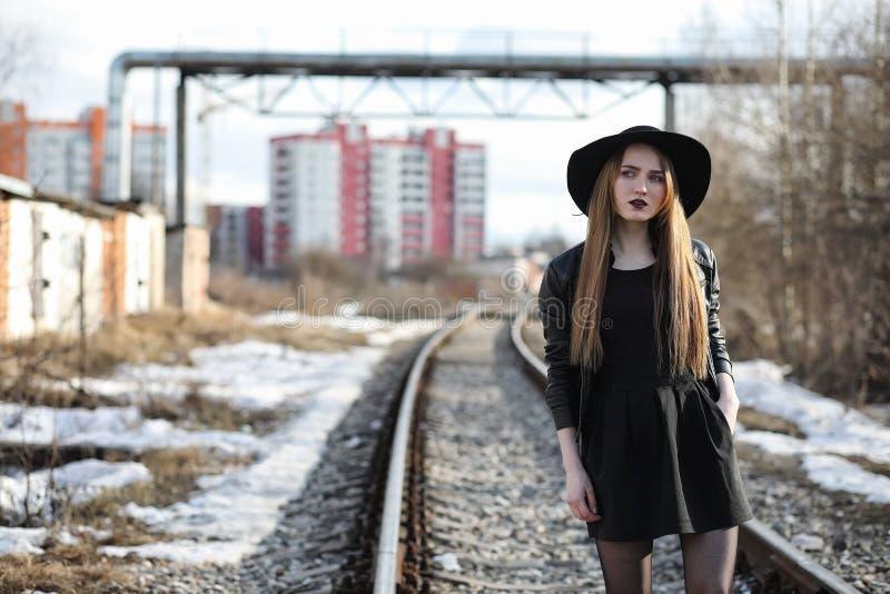 Junges schönes Mädchen in einem Hut und mit einem dunklen Make-up draußen g stockbilder