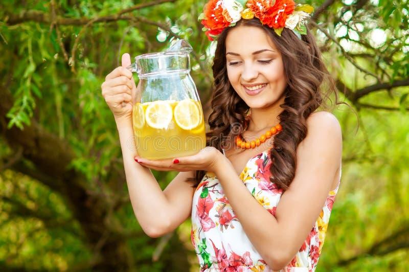 Junges schönes Mädchen in einem Kranz von Blumen mit Limonade lizenzfreies stockbild
