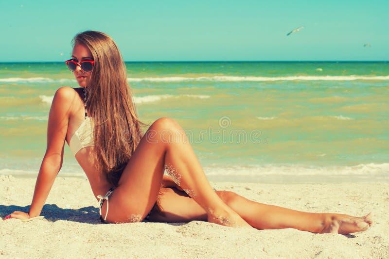 Junges schönes Mädchen im Badeanzug und in der Sonnenbrille am Strand stockbild