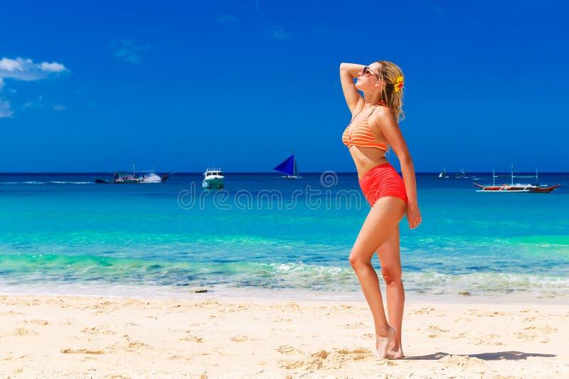 Junges schönes Mädchen im Bikini steht auf dem Strand Blauer tr stockfotografie