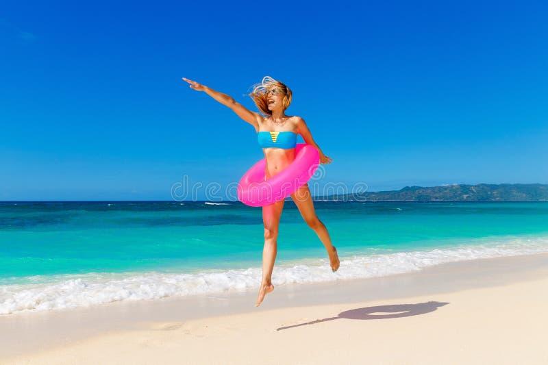 Junges schönes Mädchen im blauen Bikini, der Spaß auf einem tropischen bea hat stockfotos